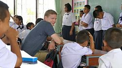 "A group of young adults on a short term overseas missions trip have fun playing ""thumbs up"" with Thai children during teaching English class in Ratchaburi, Thailand."