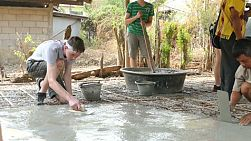 A group of high school students on an overseas missions trip work hard pouring concrete on a construction project in a Karen hill tribe village in Chiang Rai, Thailand.