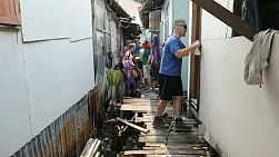 A group of high school students on an overseas missions trip work hard on a construction project in the slums of Bangkok, Thailand.