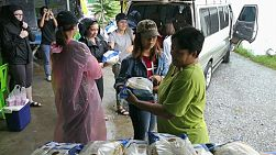 A group of young people on a short-term missions trip prepare to hand out bags of rice to elderly people living in the slums of Bangkok, Thailand.