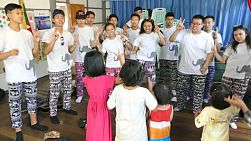 A group of high school students on an overseas missions trip sings action songs to kids in a rural village outside Myawaddy, Burma.