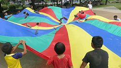 A group of cute Asian kids and a foreign youth missions team have fun playing parachute game in Pattaya, Thailand.