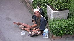 A lonely Muslim Asian man waits patiently for people to give him money as he begs on the streets of Bangkok, Thailand.