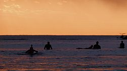 Silhouettes of surfers on the water at South Cottesloe Beach in Western Australia, as the sun sets in the background.