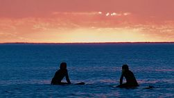 Silhouettes of surfers sitting on their boards waiting for a wave at South Cottesloe Beach in Western Australia, as the sun sets in the background.