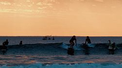 Silhouettes of a group of surfers at South Cottesloe Beach in Western Australia, as the sun sets in the background.