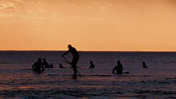 Silhouettes of surfers and a paddleboarder at South Cottesloe Beach in Western Australia, as the sun sets in the background.