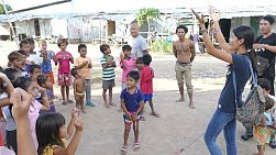 A group of Khmer young adults on an overseas missions trip to Thailand sing action songs to kids in a Khmer Migrant Worker Camp in Pattaya, Thailand.