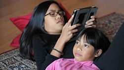 Two cute Asian sisters have a bit of a disagreement while spending time together playing on their new digital tablet in the living room.