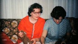 Two sisters opening even more Christmas presents in 1960.