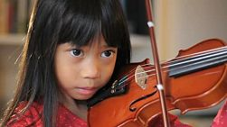 A close up shot of a pretty 6 year-old Asian girl diligently practices her violin in the living room.