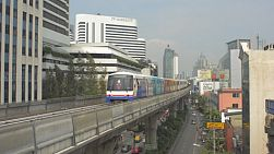 BANGKOK, THAILAND - OCTOBER 9 2013: The BTS skytrain running past skyscrapers and buildings,  heading towards the camera, along Sukhumwit Road in Bangkok, Thailand.