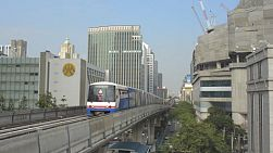 BANGKOK, THAILAND - OCTOBER 9 2013: The BTS skytrain running past skyscrapers and buildings, towards the camera, in Bangkok, Thailand.