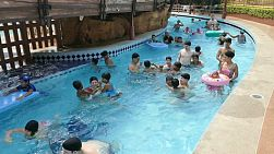 A group of high school students having fun with Thai children from the slums at a water park in Bangkok, Thailand.