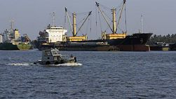 A small boat traveling up the Chao Phraya River past empty cargo ships in Bangkok, Thailand.