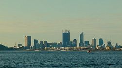 View across the water of the Swan River, to the Perth City Skyline, with a small boat passing by in the foreground.
