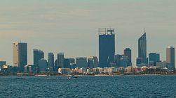 View across the water of the Swan River, to the Perth City Skyline, with a small boat passing by.