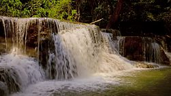 Water cascading over a small tiered waterfall, part of the Huay Mae Khamin waterfalls in Kanchanaburi, Thailand.