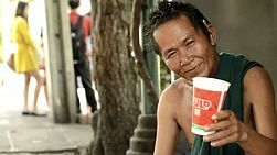 Rough looking beggar smiling, while on the streets of Bangkok, Thailand.