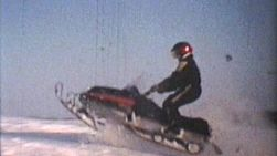 A cool collection of snowmobile jumping over snow drifts and racing around and having fun! (1975 - Vintage 8mm film)