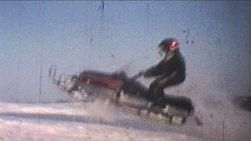 A couple of guys try doing some jumping with their snowmobiles on a cold winter's day.