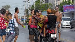 Bangkok, Thailand - April 14, 2014: People on a motorbike getting stopped and splashed with water during the water fights of Songkran Festival in Thailand.