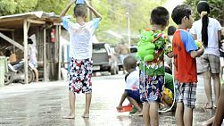 Bangkok, Thailand - April 13, 2012: Children enjoying the annual Songkran festivities with a water fight.  Songkran is traditionally the Thai New Year, and as part of the celebrations, pouring water over other people is done as a way of blessing them. This has escalated to major water fights on the streets, with people pouring water on, or throwing water over anyone who passes by.  [binicons]293727 h 21 icon[/binicons]