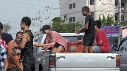 Bangkok, Thailand - April 14, 2014: People engaging in a water fight during the Songkran Festival, from the back of a truck, splashing water and powdering faces.