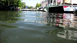 A low angle shot of several speed boats in a massively flooded street in Bangkok, Thailand.