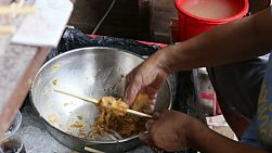 A Thai street food vendor prepares a special meat paste to create spicy kebabs in Bangkok, Thailand.