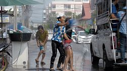 Bangkok, Thailand - April 14, 2014: Group of youth splashing people on the back of a passing songtaew truck, during the Songkran Festival water fights in Thailand.