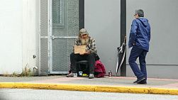 VANCOUVER, BC, OCTOBER 2015: An old homeless man living on the streets receives some money from a kind stranger on the streets of Vancouver, BC.