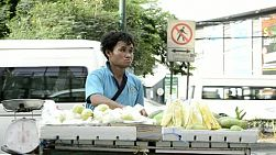 Man selling fruit from a cart on the sidewalk near a busy road in Bangkok, Thailand.
