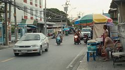 Street vendors, traffic and people on a suburban street in Bangkok, Thailand.