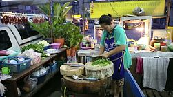 A Thai street vendor slices and dices fresh vegetables as she prepares another delicious meal at the market in Bangkok, Thailand.