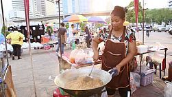 A Thai lady frying a huge wok full of Pad Thai noodles at her stall on the streets of Bangkok, Thailand.