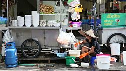 An Asian lady takes time to wash her dirty pots and pans on the streets of Bangkok, Thailand.