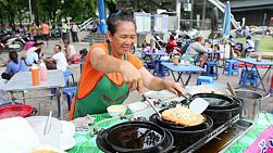 A Thai lady makes a delicious egg omelette on the streets of Bangkok, Thailand.