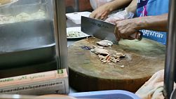 "A street vendor chops up chicken and puts in on rice as he prepares plates of ""Khao Man Gai"" in Bangkok, Thailand."