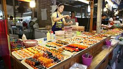 A Thai street food vendor selling fresh sushi at the market in Bangkok, Thailand.