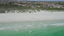 Aerial view tilting up from clear water to suburban landscape at Mullaloo Beach in Perth, Western Australia.