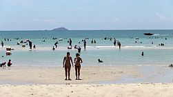 A pair of beautiful sunbathing women take a swim in the ocean to cool off while on holidays in Sattahip, Thailand.