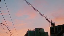Colourful sky at sunset behind a high rise construction site.