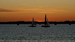 Yachts sailing on Perth's Swan River as the sun sets on the horizon.