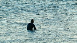 A man surfing, sitting on his surfboard in the water, waiting for the next wave.