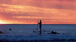 Surfers waiting for a wave on quiet water at South Cottesloe Beach in Western Australia, as the sun sets in the background.