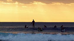 Surfers at South Cottesloe Beach in Western Australia, with a fiery sunset in the background.