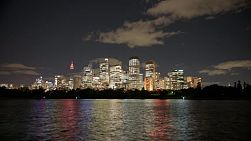 Night time lapse of the Sydney City skyline with the city lights reflecting off the harbour water surface.