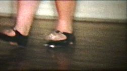 A slow motion home movie clip of a girl tap dancing.