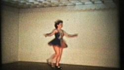 A beautiful teenage girl wearing a pretty dress performs a lovely tap dance routine at her recital.